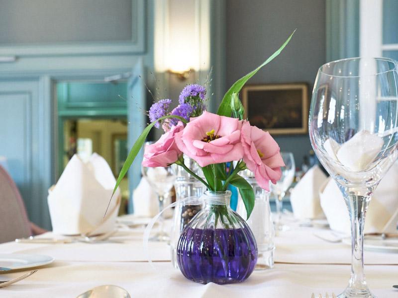 Blumenvase mit bunten Blumen auf Tisch mit weißem Tischtuch