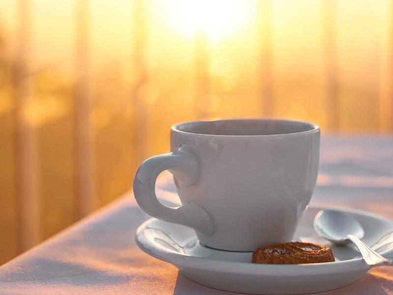 Weiße Kaffeetasse auf Tisch von Sonne angeleuchtet